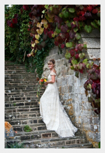Wedding dress by Felicity Westmacott, Empire line wedding dress in pale gold silk satin and beaded lace: the train trailing up some steps
