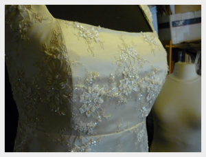 Wedding dress by Felicity Westmacott, Empire line wedding dress in pale gold silk satin and beaded lace: detail of the beaded lace bodice on the stand