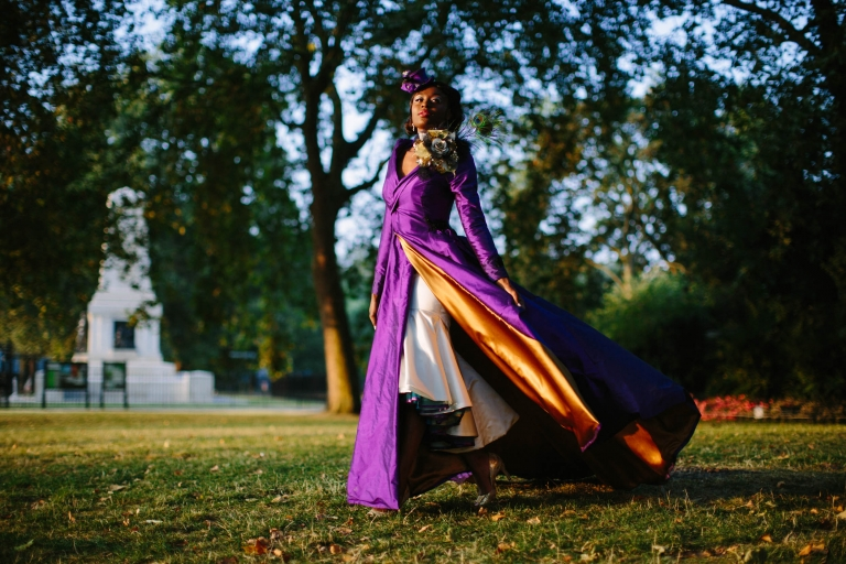 Design by Felicity Westmacott, Photography by Jessica Partridge, Burlesque inspired Purple silk wedding coat with statement collar and sweeping train: Model walks showing the gold coat lining, near Horse Guards Parade, London