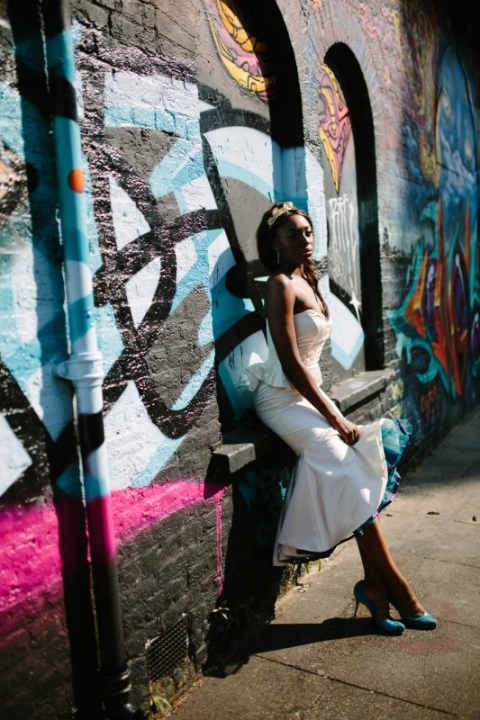 Design by Felicity Westmacott, Photography by Jessica Partridge, Burlesque inspired wedding dress in ivory satin with peplum, lace and teal net petticoat: model perches on graffiti wall, Brick Lane