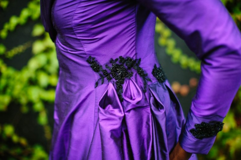 Design by Felicity Westmacott, Photography by Jessica Partridge, Burlesque inspired Purple silk wedding coat with statement collar and sweeping train: detail of petal folds and black lace applique on the hip