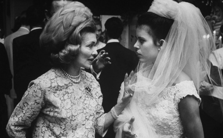 Mother of the bride admoshing a bride in her dress and veil, 1960's