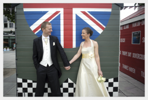 Wedding dress by Felicity Westmacott: cream silk with yellow sash and halter neck, wedding picture in front of the union flag