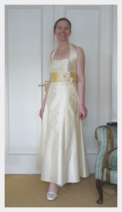 Wedding dress by Felicity Westmacott: cream silk with yellow sash and halter neck: fitting picture with rose corsage