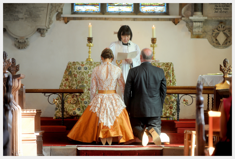 Wedding Dress by Felicity Westmacott, Autumnal orange silk dress with ivory lace and 1950's flare: kneeling at the altar