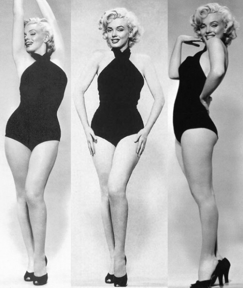 Marilyn Monroe poses in a figure hugging black swimsuit, showing off her hourglass figure