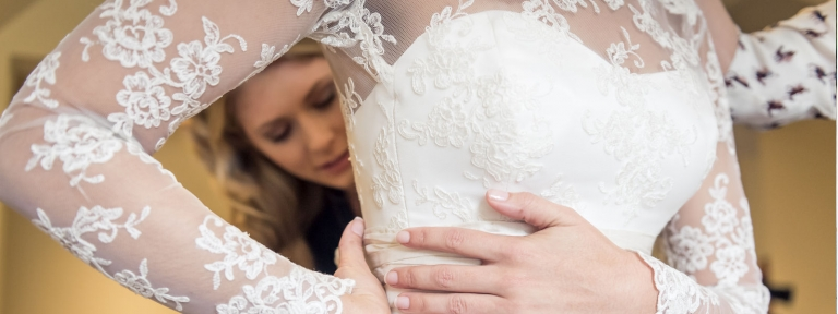 Corded lace wedding dress bodice being fastened, Felicity Westmacott, photography by montysteedman