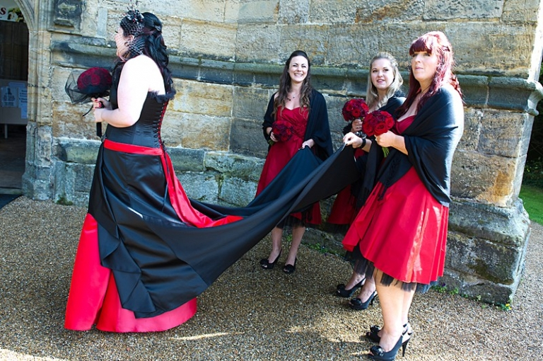 faye 2 alternative wedding dress with long black train and bridesmaids
