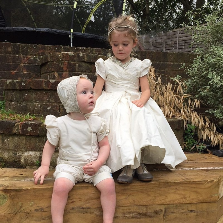 sisters sitting together in the garden, baby romper and bonnet custom made to measure puff sleeves flowergirl dress