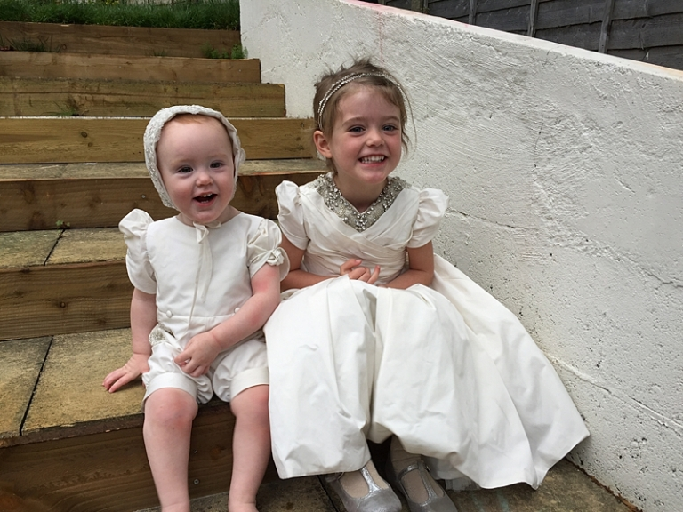 outfits being worn on the day, sisters in matching puff sleeve ivory and silver dress and romper