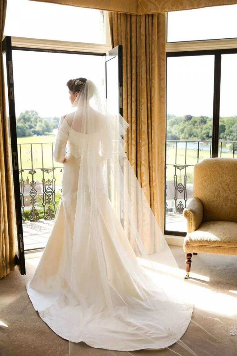graceful window lit bride with veil and train